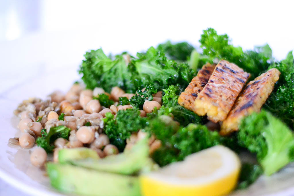 This chopped kale salad is drizzled with a fresh lemon vinaigrette and topped with sizzling grilled tempeh. Guaranteed to delight your tastebuds and fill you up fast! #vegan #salad #recipes